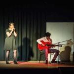 Une jeune fille chante accompagnée d'un guitariste